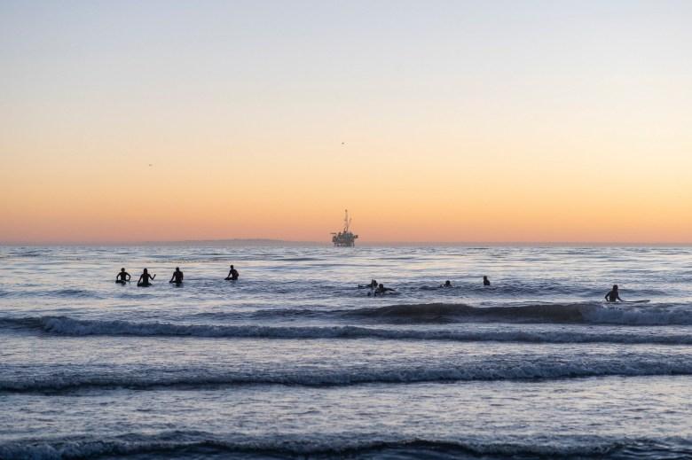 Los surfistas se reúnen en el Océano Pacífico frente a la costa de Coal Oil Point Reserve en Isla Vista, una playa popular para los estudiantes de UC Santa Bárbara, en la noche del 12 de noviembre de 2020. Foto de Max Abrams para CalMatters