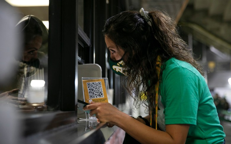 """Talat Mirmalek, de San Francisco, habla con un empleado de concesiones mientras lucha por usar la aplicación de pedidos y pagos en línea. """"Nos estamos perdiendo toda la primera mitad del juego en este momento"""", dijo su amiga Sierra Coats con frustración. Foto de Anne Wernikoff, CalMatters"""