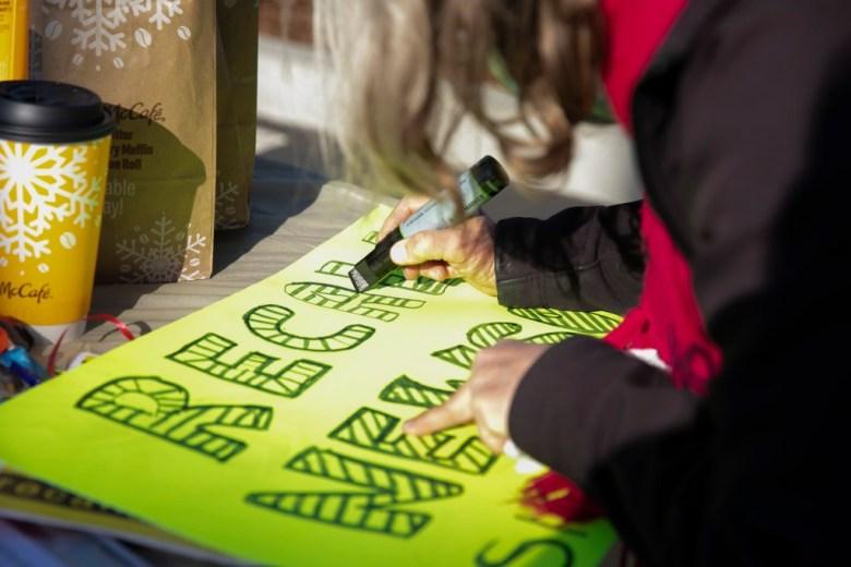 Recordemos que el voluntario de Newsom, Pat Miller, hace un letrero durante un evento de firma de peticiones en SaveMart en Sacramento el 5 de enero de 2021. Foto de Anne Wernikoff, CalMatters