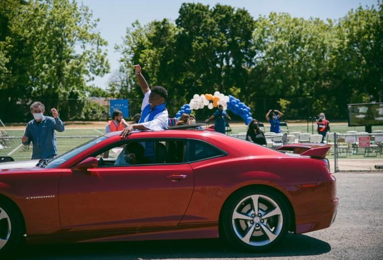 Sir aplaude desde el techo corredizo de un automóvil mientras se aleja para hacer espacio para la siguiente ceremonia de graduación en Madison Park Academy el 21 de mayo de 2021. Foto de Marissa Leshnov para CalMatters