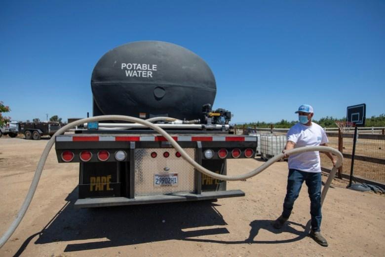 Un empleado de Bubba's Water Truck Service desenreda una manguera en preparación para bombear agua al nuevo tanque de agua de Luzvianey González en Madera el 10 de junio de 2021. Foto de Shae Hammond para CalMatters