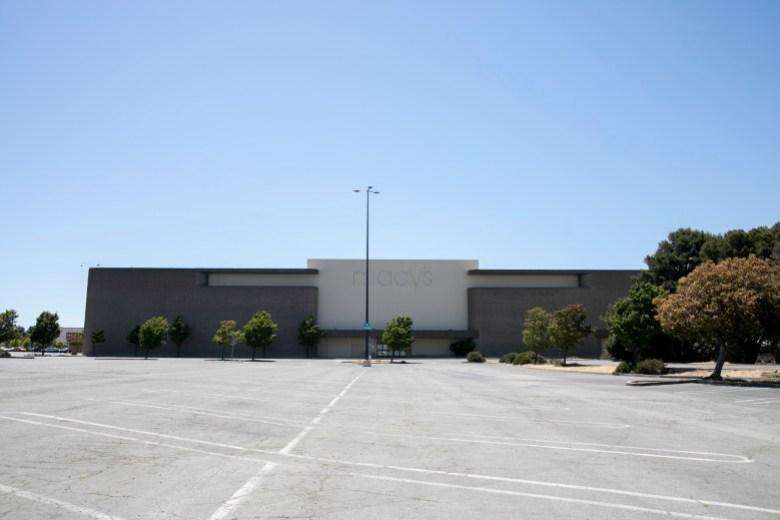 Una tienda Macy's cerrada se cierne sobre un estacionamiento vacío en Hilltop Mall en Richmond el 10 de junio de 2021. La propiedad fue comprada recientemente por los propietarios de propiedades industriales Prologis quienes, según SFGate, tienen la intención de usar la propiedad vacía para un desarrollo de uso mixto que incluye alojamiento. Foto de Anne Wernikoff, CalMatters