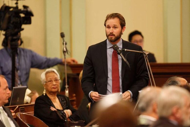 James Gallagher habla por un micrófono en el piso de la asamblea.