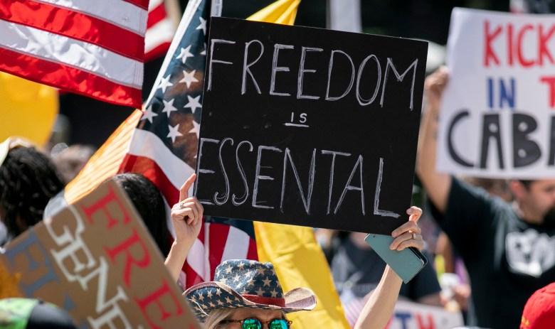 Los manifestantes sostienen carteles durante una protesta para reabrir California en el Capitolio del Estado en Sacramento el 1 de mayo de 2020. Foto de Anne Wernikoff, CalMatters