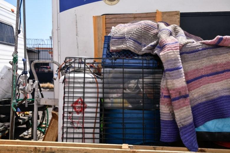 Las pertenencias de Rafael Suárez y April Lei se empaquetan afuera de la casa rodante en Los Ángeles, el 9 de julio de 2021. Además del generador, la pareja depende de su tanque de propano para cocinar alimentos y recipientes de plástico para almacenar suministros y ropa . Pablo Unzueta para CalMatters
