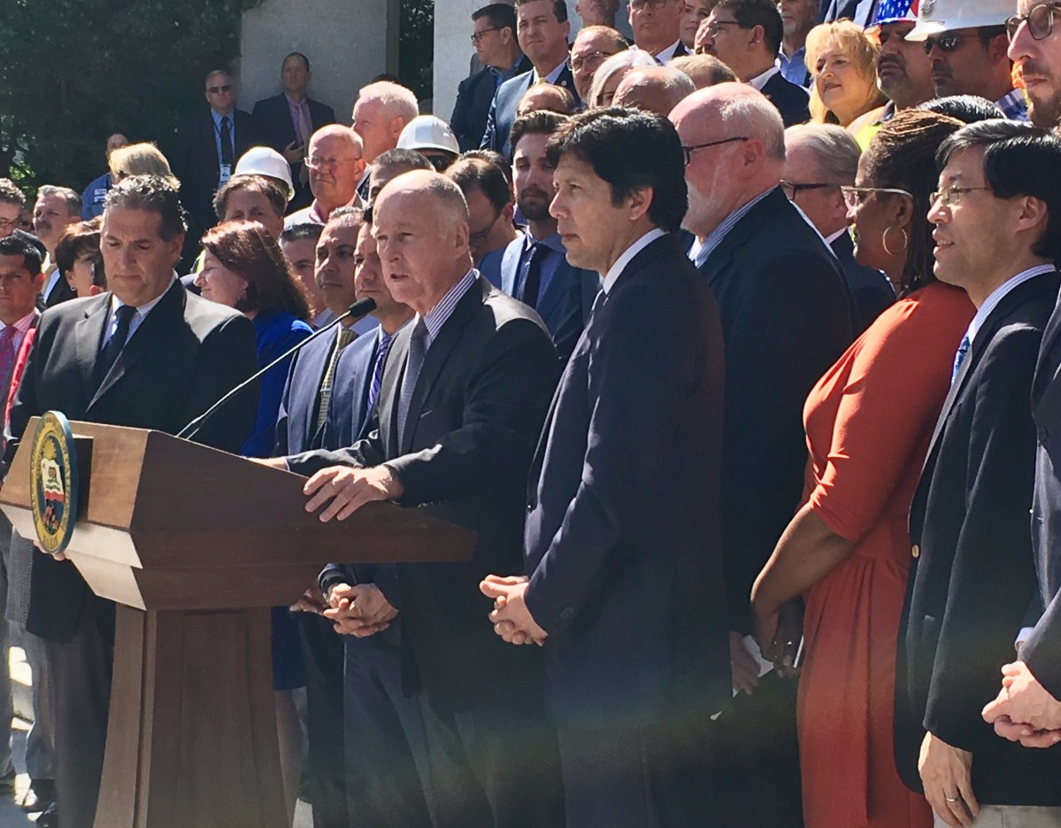 Gov. Jerry Brown, flanked by Democratic legislative leaders and construction workers, announces $52 billion plan to repair state roads. Photo by Laurel Rosenhall, CALmatters