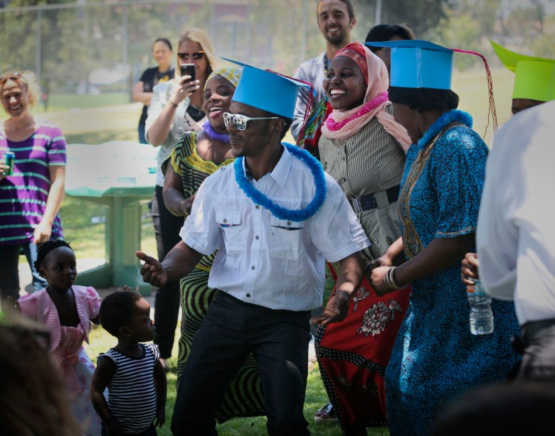 Ramazani Ali leads a group of fellow student graduates in dancing at a San Diego park. Photo by Peggy Peattie for CALmatters