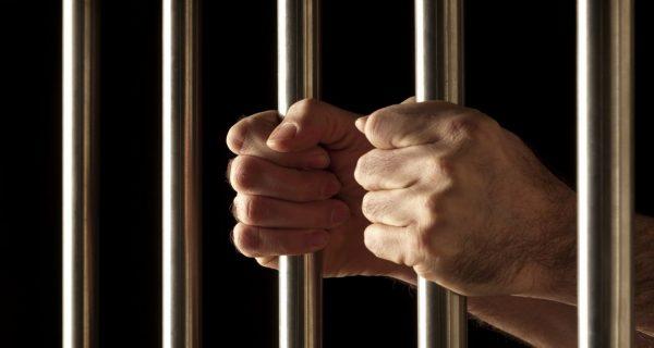 Prisoner hands on jail bars