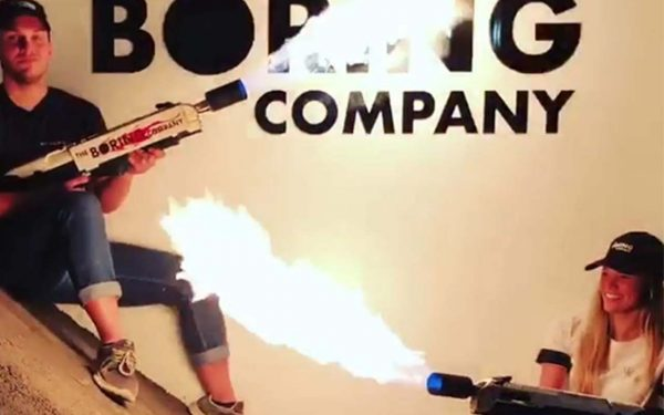 Two people hold Boring Company flamethrowers.