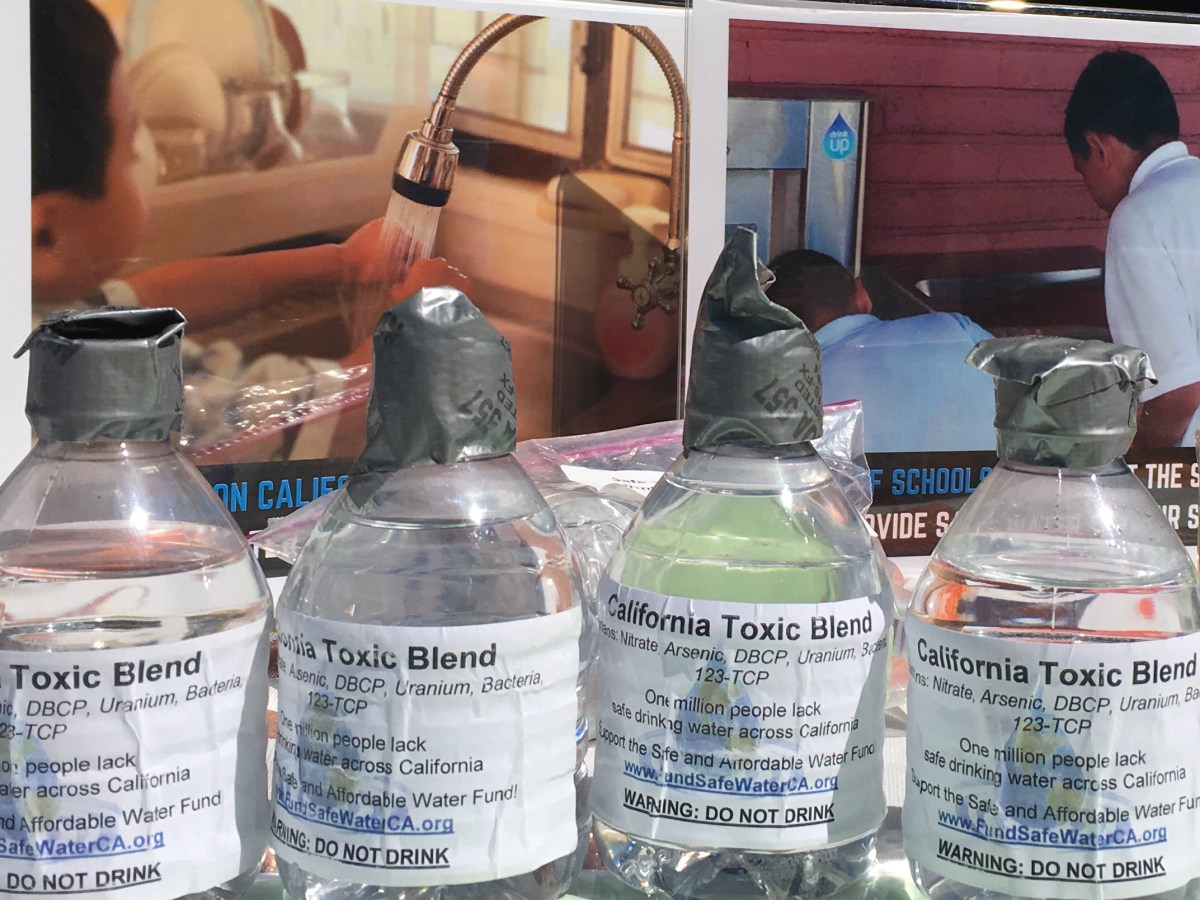 Photo: Bottles of water on display at a 2018 Sacramento rally. Photo by Antoinette Siu/CALmatters