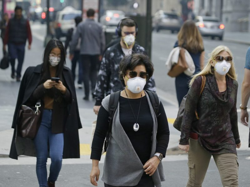 People have become accustomed to wearing masks while walking in San Francisco's Financial District and much of Northern California in the wake of the Camp Fire. Photo by Eric Risberg/Associated Press