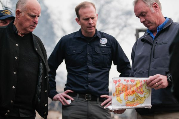 California Gov. Jerry Brown, left, and FEMA administrator Brock Long, center, watch U.S. Secretary of the Interior Ryan Zinke, right, go through school work that was recovered from Paradise Elementary School in Paradise, Calif., on Wednesday, Nov. 14, 2018. (Randy Vazquez/Bay Area News Group)