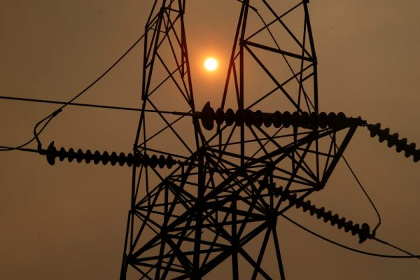 BUTTE COUNTY, CALIFORNIA - NOVEMBER 12: The sun peaks through the smokey skies from the Camp Fire and a PG&E transmission line, Monday, November 12, 2018, three miles west of Pulga, Calif. (Karl Mondon/Bay Area News Group)