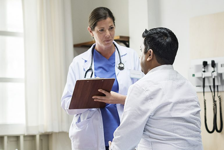 Single-payer health care isn't in California's immediate future, but Gov. Newsom is pursuing less ambitious tactics to get health coverage for more people. Here, a doctor consults wit her patient.