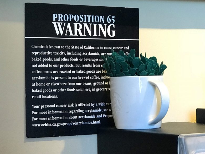 A posted Proposition 65 warning sign behind a coffee mug at a Starbucks coffee shop in Burbank, Calif. File photo by Damian Dovarganes, Associated Press