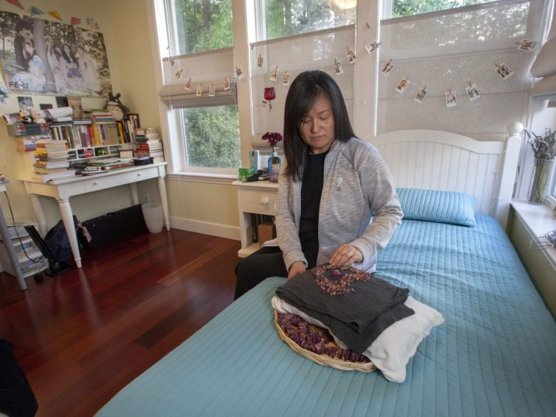 In her daughter's room, Seong Brown adjusts rose petals atop the clothing she wore when she died. Photo by Penni Gladstone for CALmatters