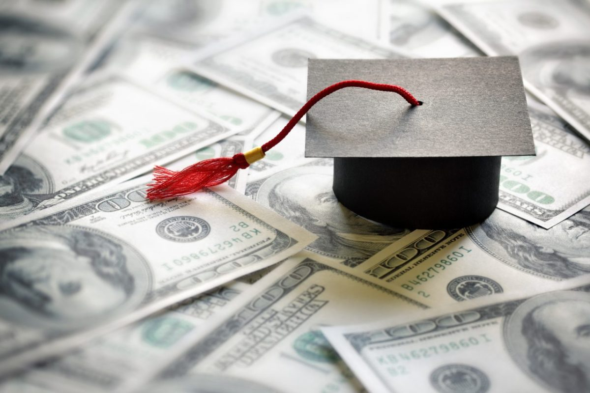 photo of Graduation mortar board cap on one hundred dollar bills concept for the cost of a college and university education