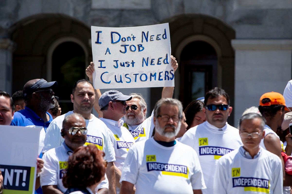 A man holds up a sign that says, 'I don't need a job, I just need customers,' during a rally in opposition to AB 5, a bill that would change the way independent contractors are classified by their employers, on July 9, 2019.