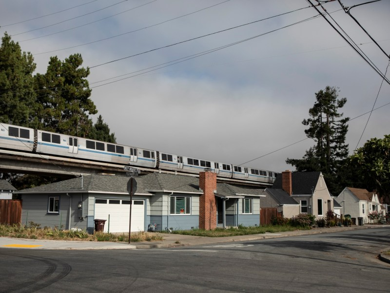 New legislation would end single-family zoning in cities across Californi. Here, a BART train runs above single family homes in Albany. Photo by Anne Wernikoff/CalMatters