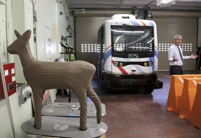 Randy Iwasaki with an autonomous bus, deer decoy and other objects in a GoMentum Station warehouse. Photo by Maria J. Avila