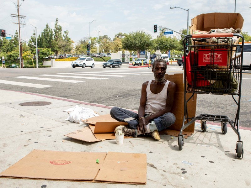 A homeless man sits on the sidewalk across from LAC+USC Medical Center in Los Angeles.