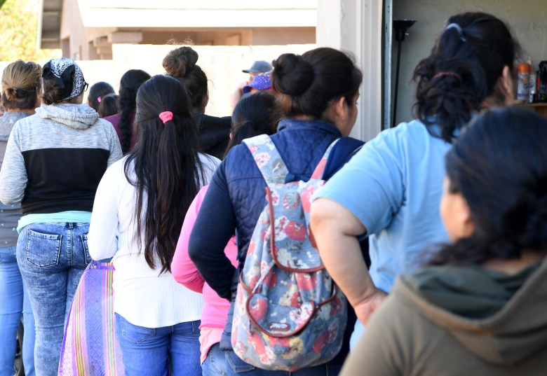 Farmworkers and families wait in line at a monthly clandestine food distribution in Santa Cruz County.