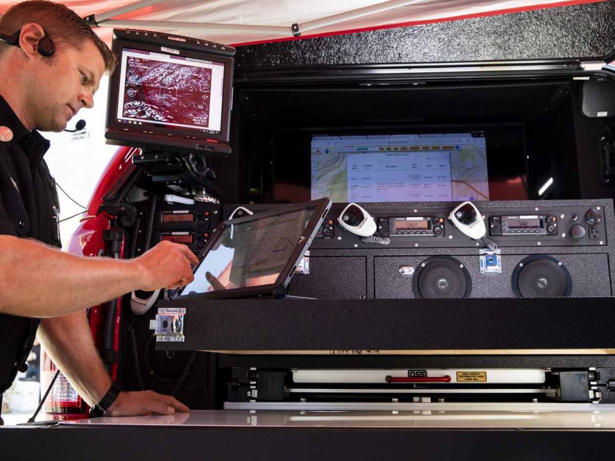 Los Angeles fire official Michael Flynn demonstrates advanced information equipment in a command vehicle, part of a California pilot program. Photo by Nancy Pastor for CalMatters