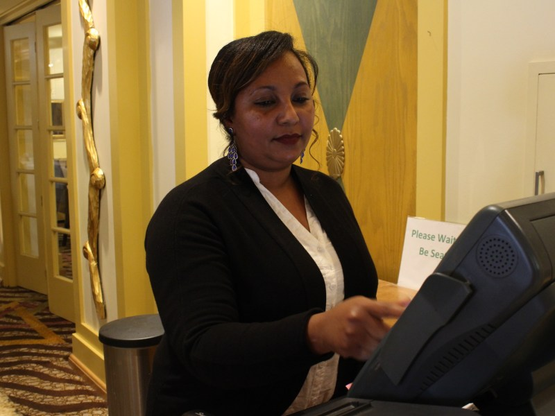 Eden Asfaha, an asylee from Eritrea, works the cashier at a Holiday Inn restaurant in San Jose. Asfaha is finishing training to be licensed as a phlebotomy technician. Photo by Farida Jhabvala Romero/KQED.
