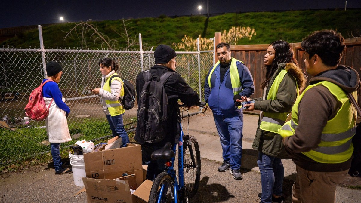 Homeless survey volunteers gather survey information from homeless people living in the Lowell neighborhood of Fresno during the January annual point-in-time homeless count. Photo by Craig Kohlruss, Fresno Bee