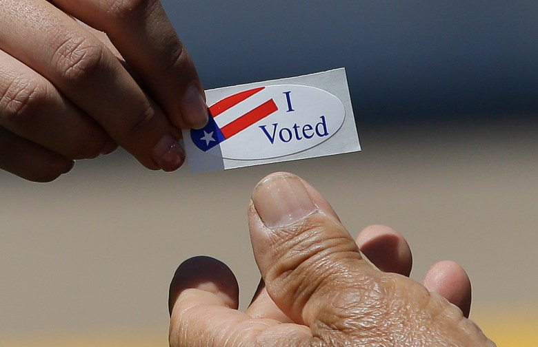 "an election worker for the Sacramento County Registrar of Voters, hands an ""I Voted"" sticker to a voter"