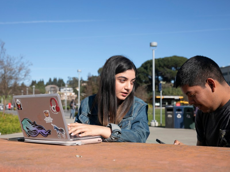 Fourth year Human Resources student Suhair Kakish, left, helps third year industrial engineering student Cesar Sanchez with his resume on campus at California State University East Bay. Photo by Anne Wernikoff for CalMatters
