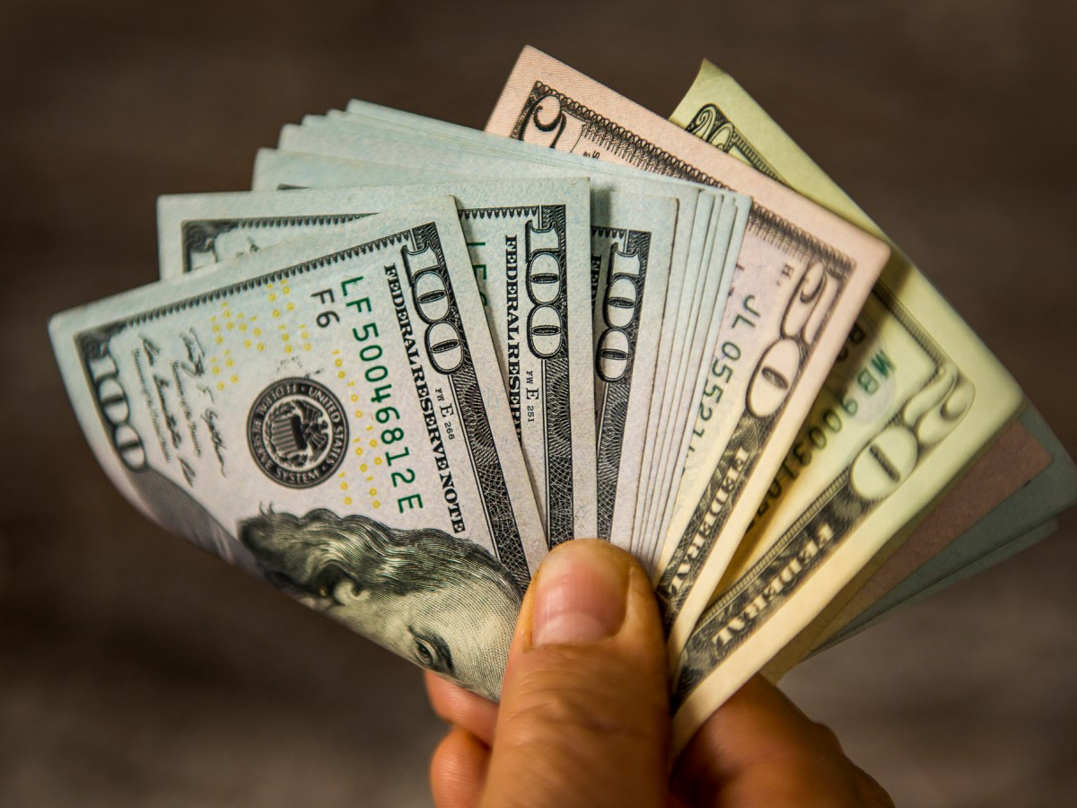 A hand holding a fistful of hundred dollar bills. With California's 2020 primary fast approaching, outside spending on California legislative campaigns is ramping up. Photo via iStock