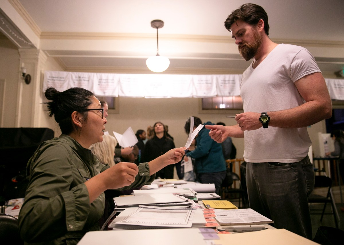 How many California ballots left to count? Here Beverly Shen distributes ballots to 2020 primary voters at the Golden Gate library in Oakland. Photo by Anne Wernikoff for CalMatters