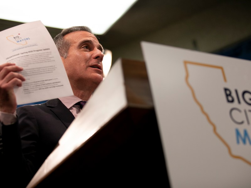 Los Angeles Mayor Eric Garcetti holds up a copy of a progress report from the Big City Mayors, a coalition of mayors from California's 13 largest cities to combat homelessness, at a press conference at the state capitol on March 9, 2020. Photo by Anne Wernikoff for CalMatters