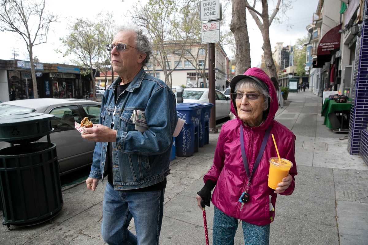 """Dolores Helman, 93, and her son Elliot Helman, 64, go for a walk in Berkeley on March 15, 2020. Dolores says she is more concerned about her grandchildren than herself, """"I'm not afraid of dying, I've had a good life,"""" she said. Earlier today Gov. Gavin Newsom called for isolation of all elderly people and those with chronic health conditions in response to growing concern over the coronavirus. Photo by Anne Wernikoff for CalMatters"""