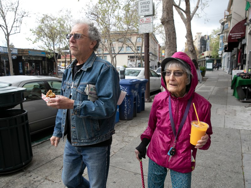 "Dolores Helman, 93, and her son Elliot Helman, 64, go for a walk in Berkeley on March 15, 2020. Dolores says she is more concerned about her grandchildren than herself, ""I'm not afraid of dying, I've had a good life,"" she said. Earlier today Gov. Gavin Newsom called for isolation of all elderly people and those with chronic health conditions in response to growing concern over the coronavirus. Photo by Anne Wernikoff for CalMatters"