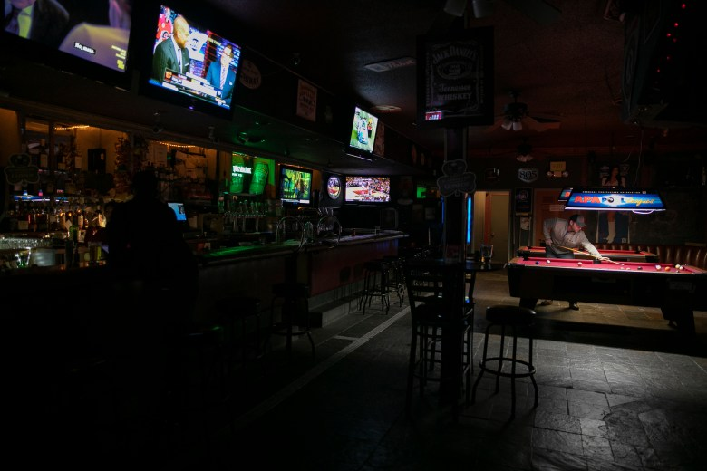 Regulars get in a last game of pool at Parkway Lounge in Oakland before the bar closes at midnight for at least three weeks. At 12:01 on March 17 six Bay Area counties will enact a shelter in place to limit to spread of the novel coronavirus. Photo by Anne Wernikoff for CalMatters
