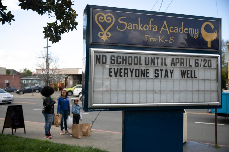 The marquee announces a district-wide school closure until April 6 at Sankofa Academy in Oakland. Children and their families from anywhere in the district can pick up multiple days worth of lunches and breakfasts from a dozen sites across the city during the mandated school closure. Photo by Anne Wernikoff for CalMatters