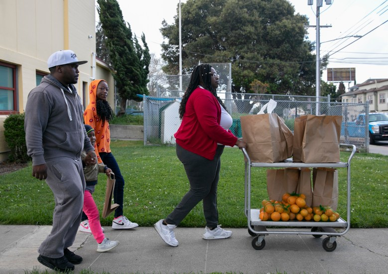 Daniel Jones, far left, with his daughter and niece, pick up two days worth of lunches and breakfasts for the family's seven children at Sankofa Academy in Oakland. Jones, a contract commercial driver, has been out of work for more than two weeks and worries about how to cover expenses after paying next month's rent. Photo by Anne Wernikoff for CalMatters