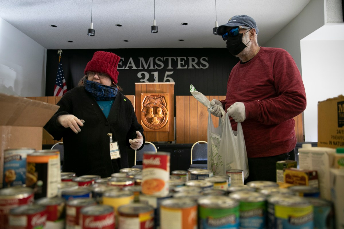 Elizabeth Hopkins, left, fills Sal Vega's shopping bag with canned goods at a food distribution site in Martinez, CA. Vega, 76, wears a mask, gloves and sunglasses to protect himself while out of the house. Photo by Anne Wernikoff for CalMatters