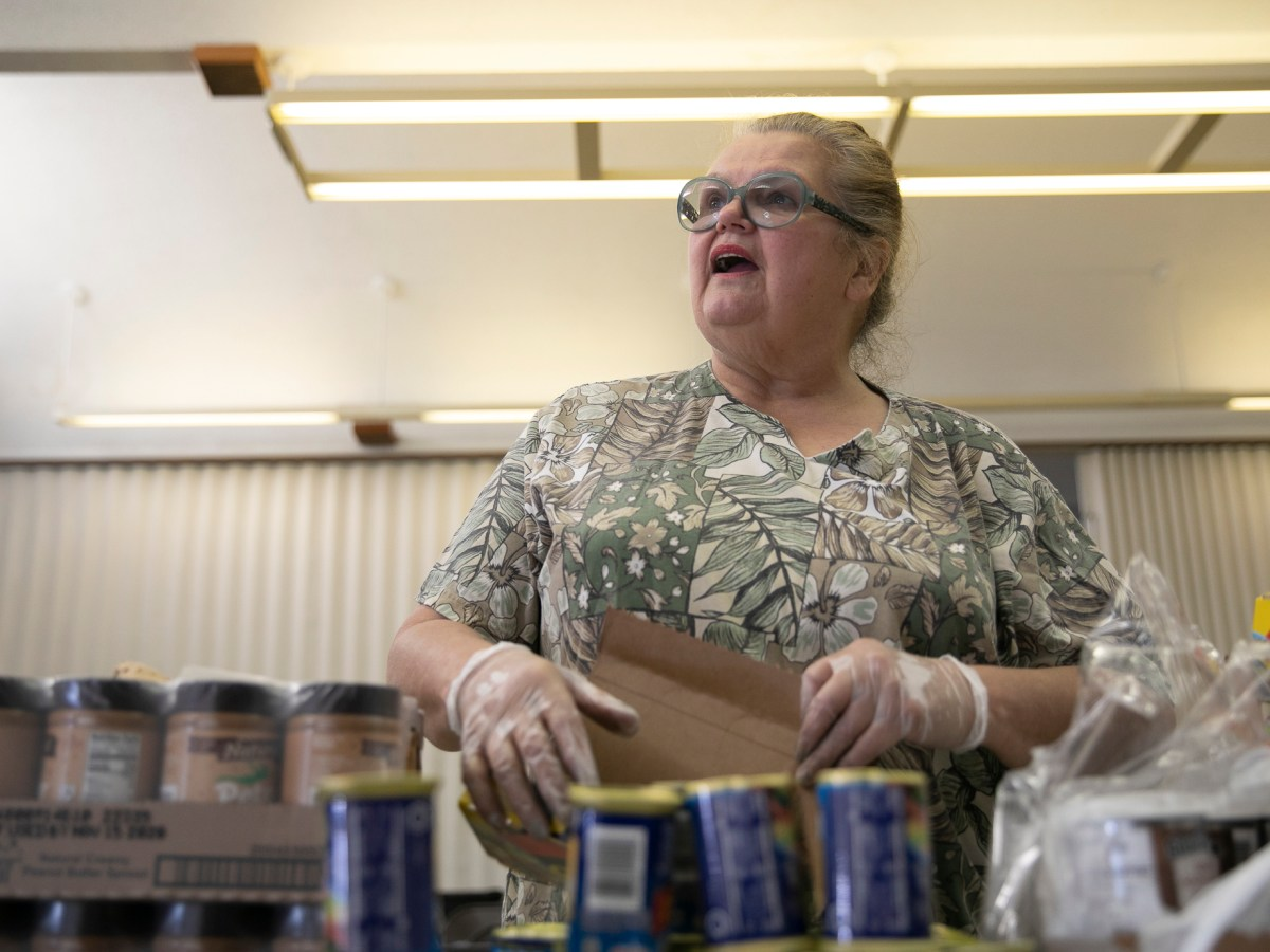 Food bank volunteer Emogene Thomas, 68, arranges cans on a table at Teamsters 315 Hall in Martinez on March 19, 2020. The food bank serves seniors but had about half regular the number of visitors due to coronavirus concerns. Photo by Anne Wernikoff for CalMatters