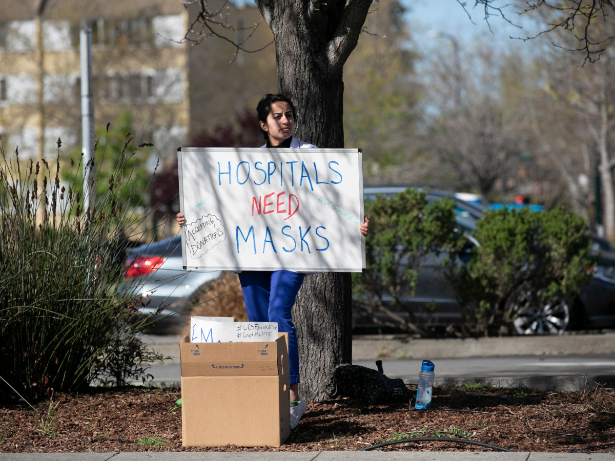 Medical student Shreya Thatai holds up a sign outside of Berkeley Bowl asking for mask donations to help health care workers. California Gov. Gavin Newsom promises to have solved the shortage by cutting a massive deal for new masks. Photo by Anne Wernikoff for CalMatters