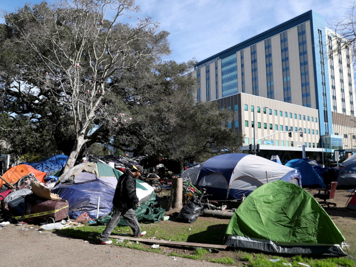 A man walks past tents as Oakland Public Works Department employees remove debris from a homeless encampment at Mosswood Park in Oakland, Calif., on Tuesday, February 4, 2020. Photo by Jane Tyska, Bay Area News Group