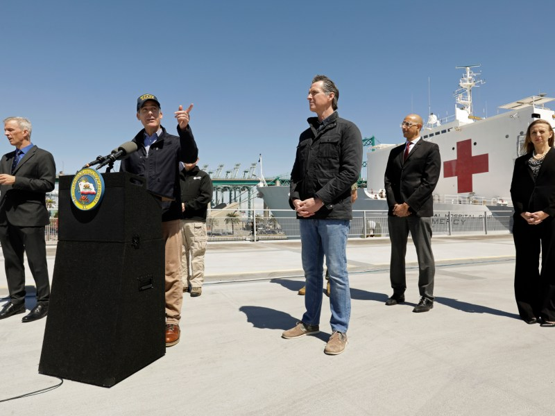 LOS ANGELES, CALIFORNIA—MARCH 27, 2020—California Governor Gavin Newsom listens as Los Angeles Mayor Eric Garcetti speaks in front of the hospital ship USNS Mercy that arrived into the Port of Los Angeles on Friday, March 27, 2020, to provide relief for Southland hospitals overwhelmed by the coronavirus pandemic. (POOL PHOTOGRAPHS BY Carolyn Cole/Los Angeles Times)