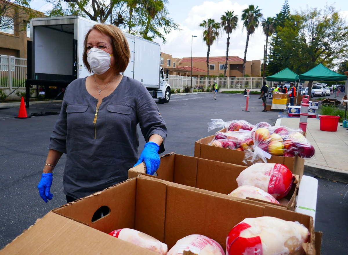 Sen. Maria Elena Durazo loads bags of meat and produce into peoples' cars at a Los Angeles food bank on April 2, 2020. Photo by Elizabeth Aguilera for CalMatters