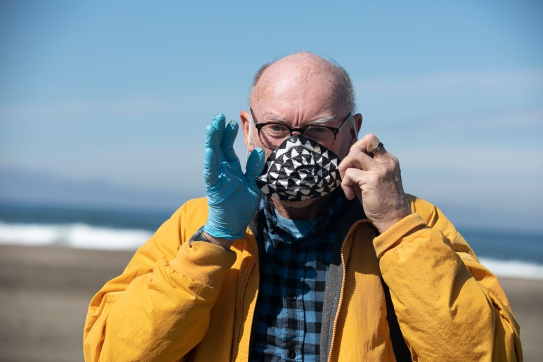 San Francisco resident Dave Mahon shows off a protective mask that he decorated in order to make 'things feel more friendly' at Ocean Beach. California is entering the fourth week of sheltering in place to limit the spread of the novel coronavirus. Photo by Anne Wernikoff for CalMatters