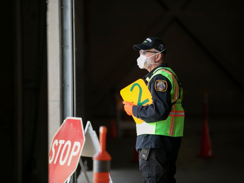 City CERT member Steve Bicker directs traffic into the drive-thru COVID-19 testing facility at Cal Expo in Sacramento. The by-appointment-only facility has been testing upwards of 300 patients per day. Photo by Anne Wernikoff for CalMatters