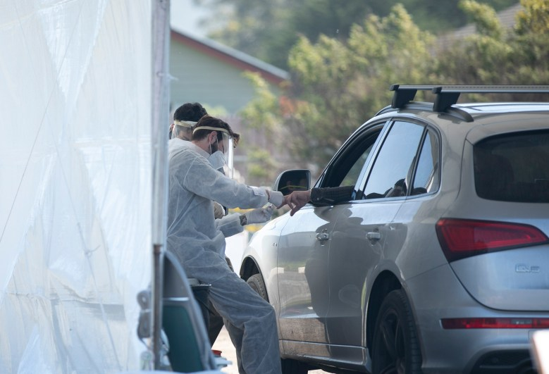 A phlebotomist takes a finger prick blood sample at a drive-thru COVID-19 testing site in Bolinas on April 22, 2020. Bolinas is attempting to test the entire town in conjunction with a UCSF study, one of the first efforts of its kind in California. Photo by Anne Wernikoff for CalMatters