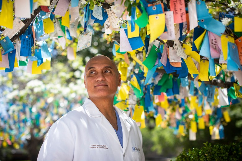 Dr. Ray Samoa at the City of Hope Comprehensive Cancer Center in Duarte on April 25, 2020. Samoa stands amongst Wishing Trees, a place where City of Hope employees and visitors offer messages of health and hope to patients and their families. Photo by Nancy Pastor for CalMatters