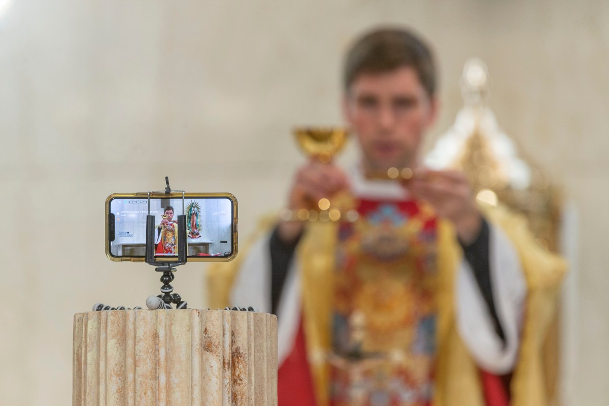 The Rev. Matthew Wheeler is seen on an iPhone screen live-streaming the celebration of the the Mass of the Lord's Supper at St. Anthony Parish in San Gabriel, Calif., Thursday, April 9, 2020. With no public Mass due to the coronavirus pandemic, the church live-streams its services. Photo by AP Damian Dovarganes, AP Photo